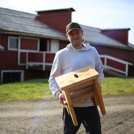 Lucas shows a cedar stool he made at Blanchet Farm in Carlton, Oregon