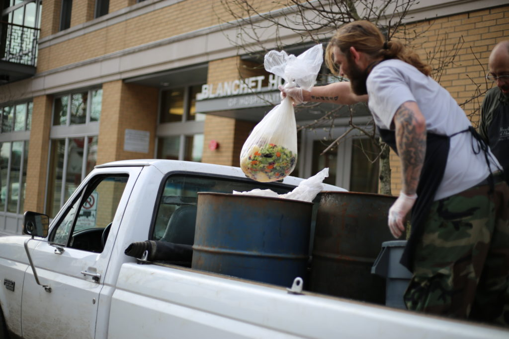 A resident of Blanchet House loads food scraps on to a farmer's truck.