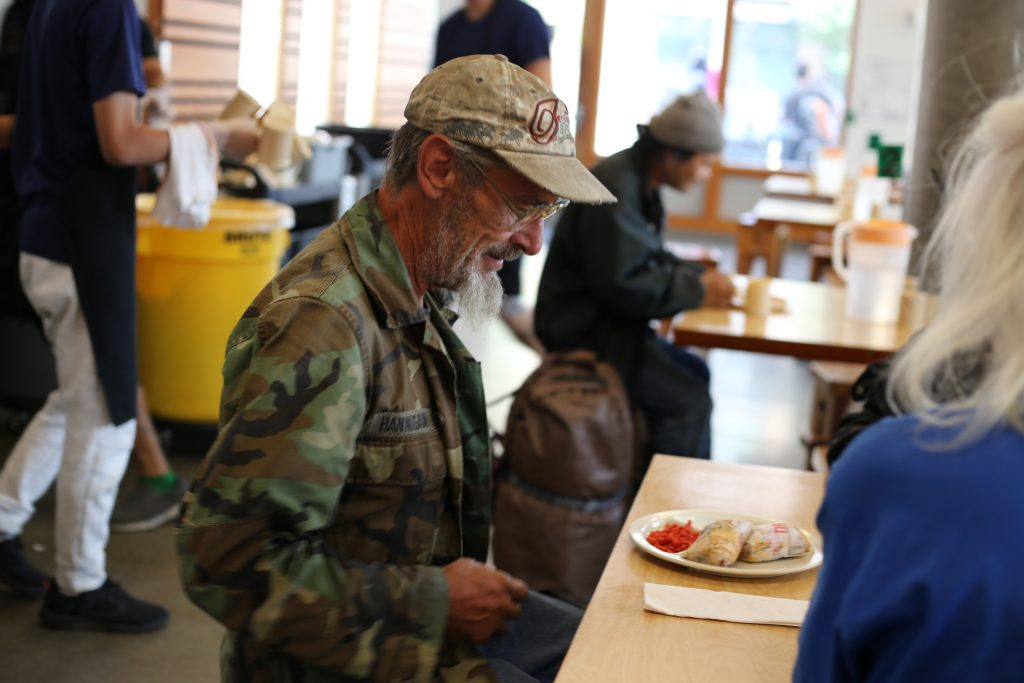 A Veteran enjoys a free meal at Blanchet House in downtown Portland, Oregon.