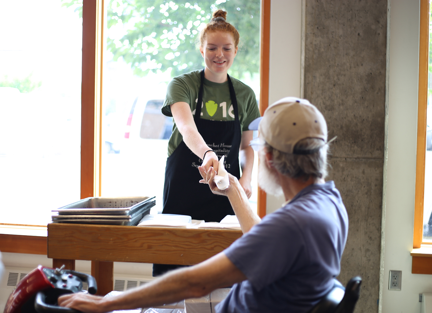 JVC/Americorps volunteer Emily Reiling handing a fork to a meal guest at Blanchet House.