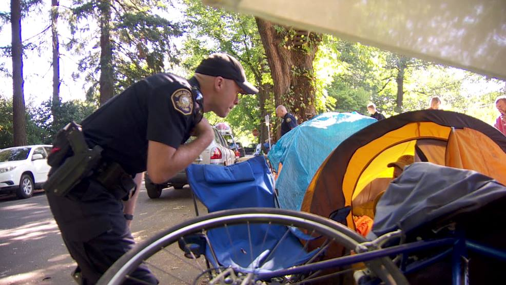 Portland Police Officer conducts a sweep of a homeless camp.