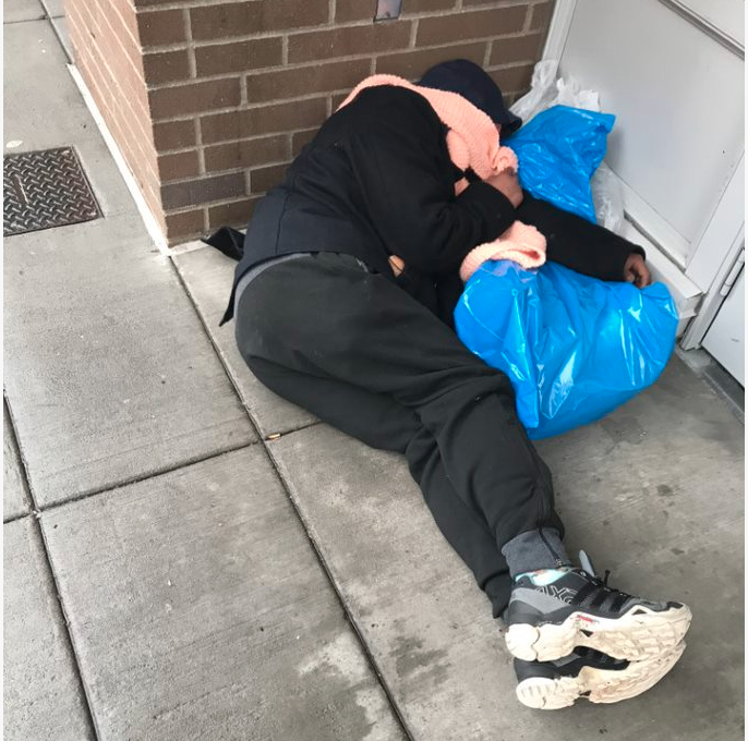 Homeless woman sleeps on the sidewalk in downtown Portland Oregon