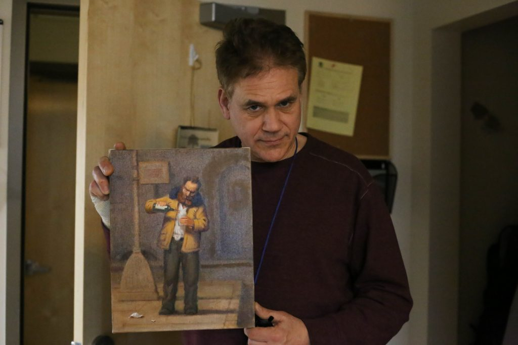 Artist Richard Lithgow poses with a recent painting he made at Blanchet House.