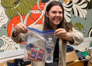 A volunteer displays a basic needs care kit.