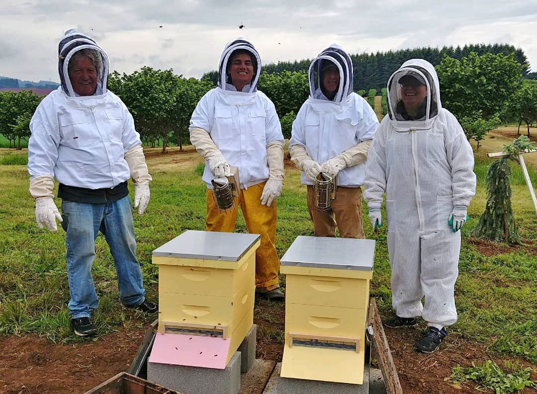 Left to right: Ron, Jordan, an anonymous guest, and Katy Fackler pose next to the hives they installed at Blanchet Farm. Photo courtesy of Blanchet House.