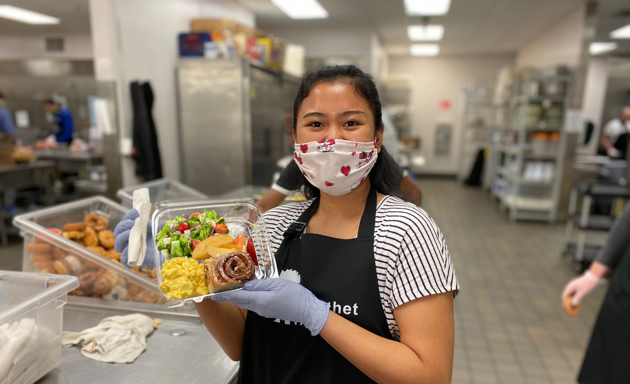 A volunteer holds a meal for the homeless at Blanchet House of Hospitality in Portland.