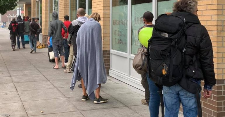 People wait in line for a free meal at Blanchet House in Portland.