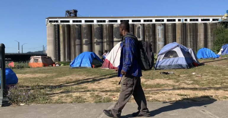 A man walks past a homeless camp in Portland along the Willamette River directly across from the Moda Center, 2020.