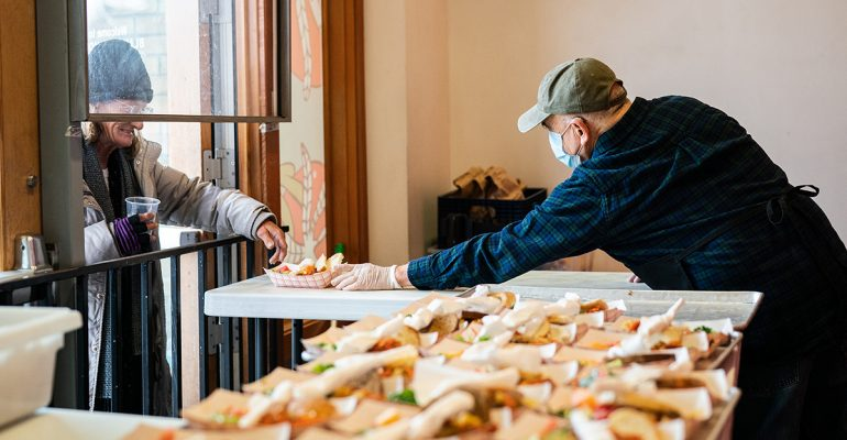 A volunteer serves a to-go meal to a guest at Blanchet House. Photo by ChristineDong
