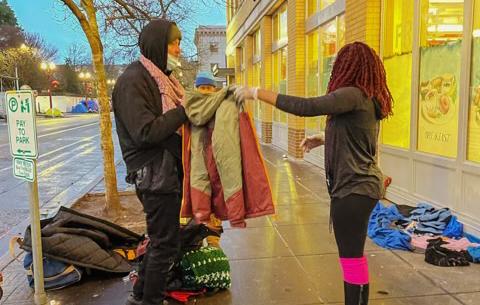 Sara Edmond offers a warm coat to a homeless man outside Blanchet House.