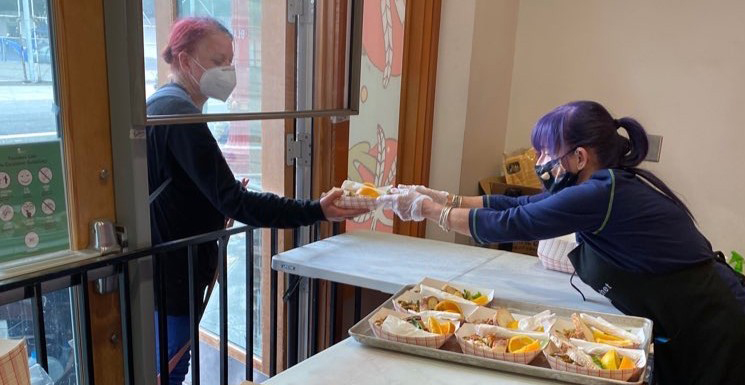 A volunteer hands a woman a free meal at Blanchet House in Portland during the COVID-19 pandemic.