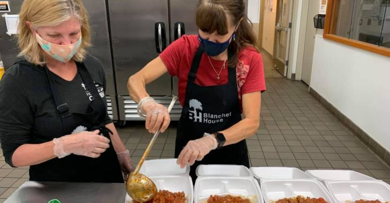 Volunteer Week Portland volunteers dish Spaghetti for homeless and food insecure guests of Blanchet House.