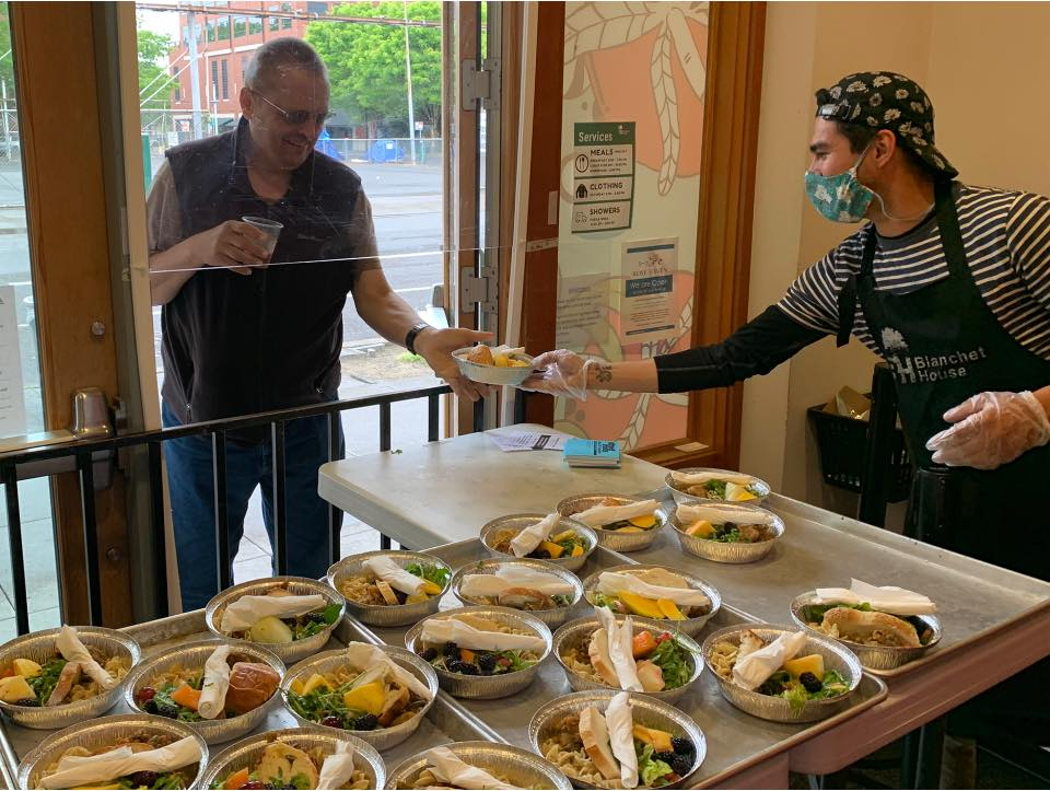 Volunteer serves a meal at Blanchet House of Hospitality in Portland.