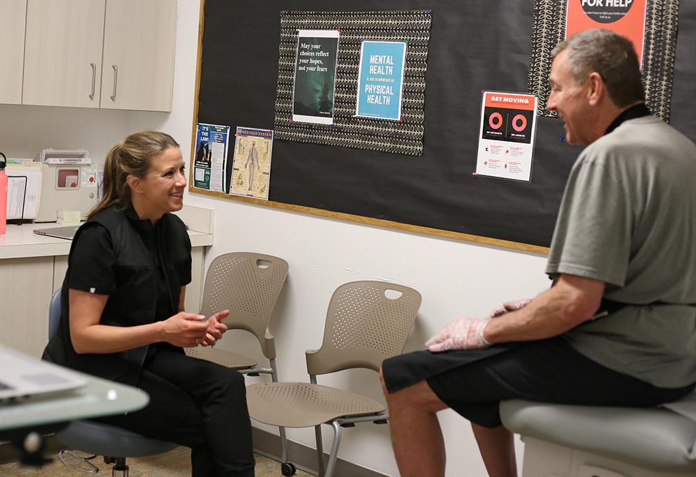 Emily Harrington talking to a guest of Blanchet House in the Harrington Health Clinic.