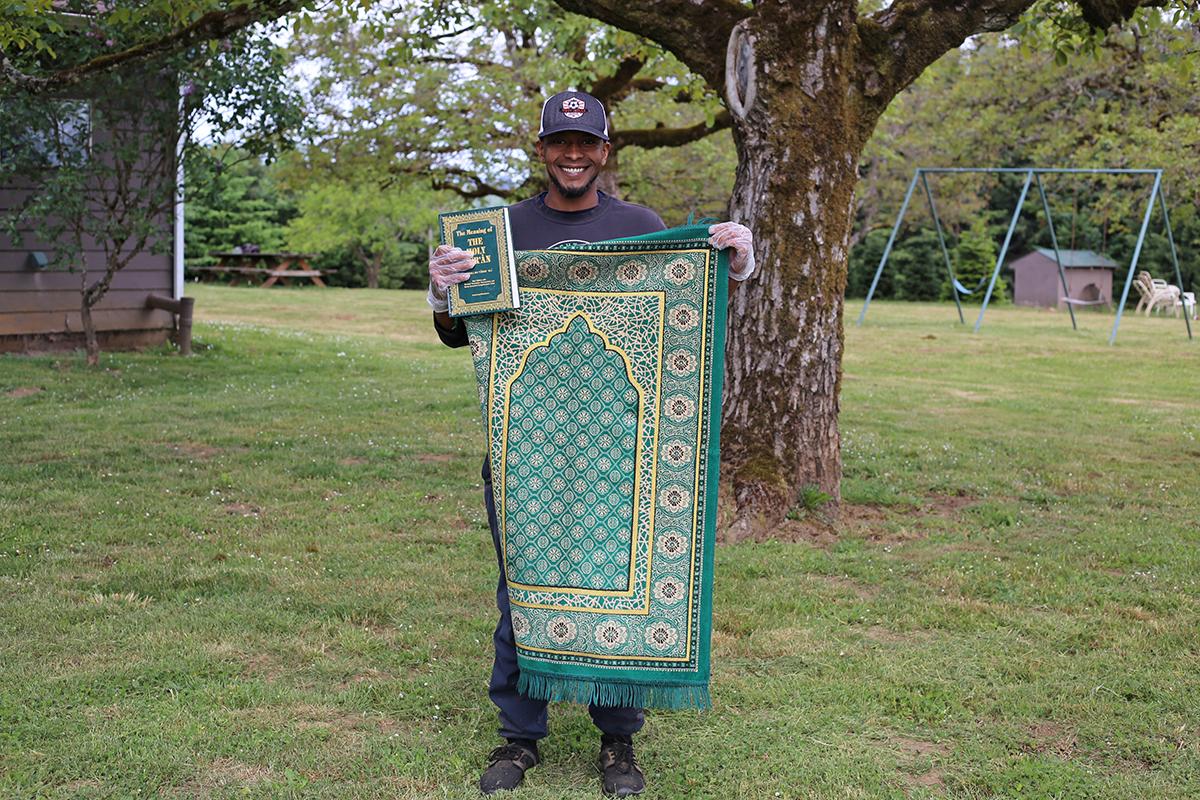Ibrahim holds his prayer rug and Koran at Blanchet Farm.