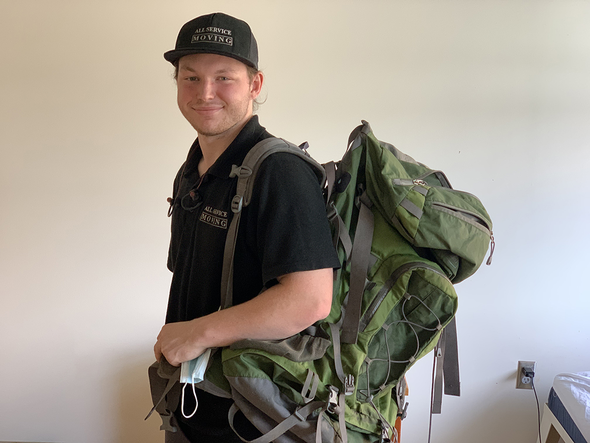 Zack holds his backpack in his room at Blanchet House in downtown Portland