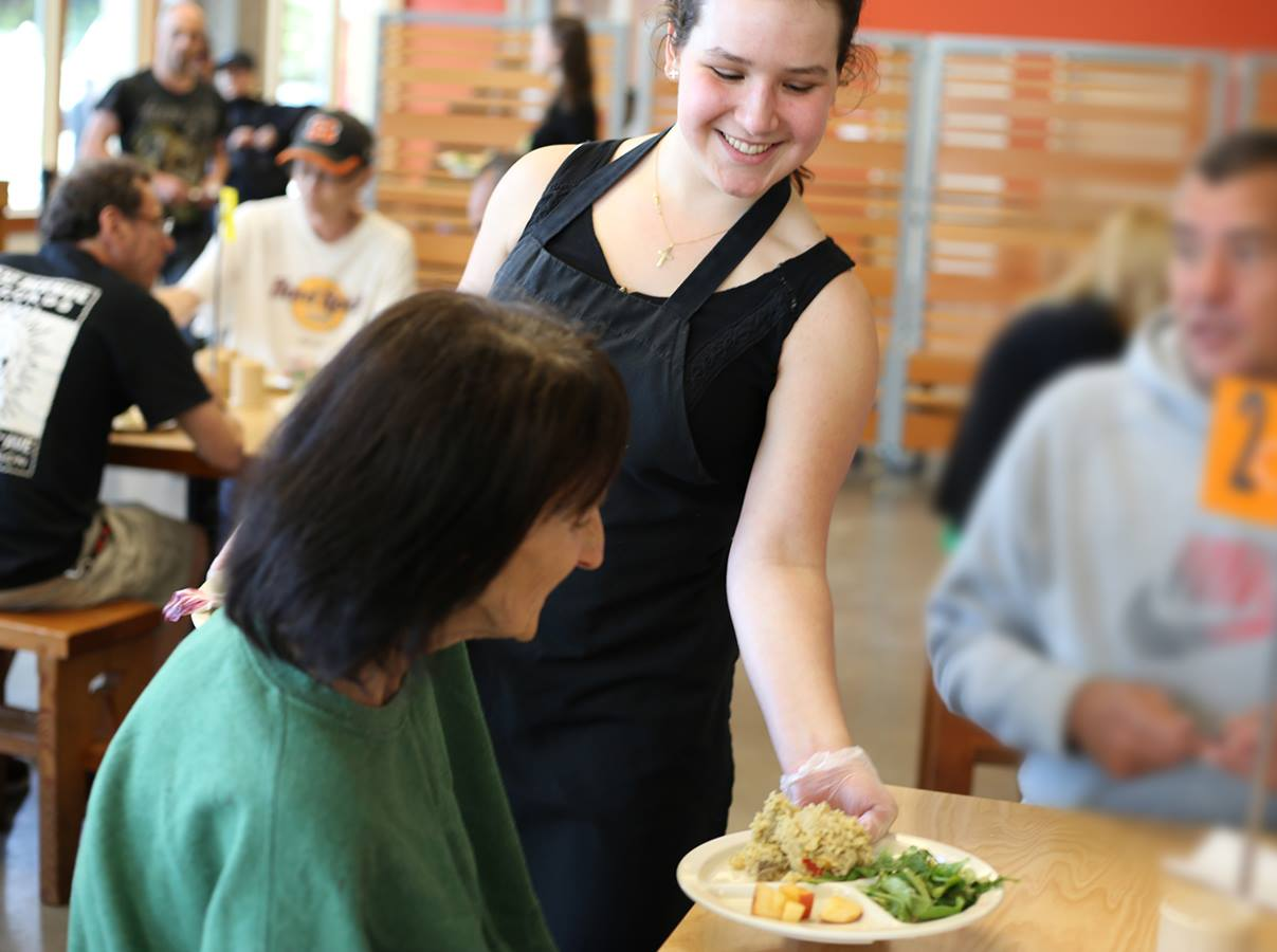 Volunteer serves a meal to a guest in Blanchet House of Hospitality's cafe.