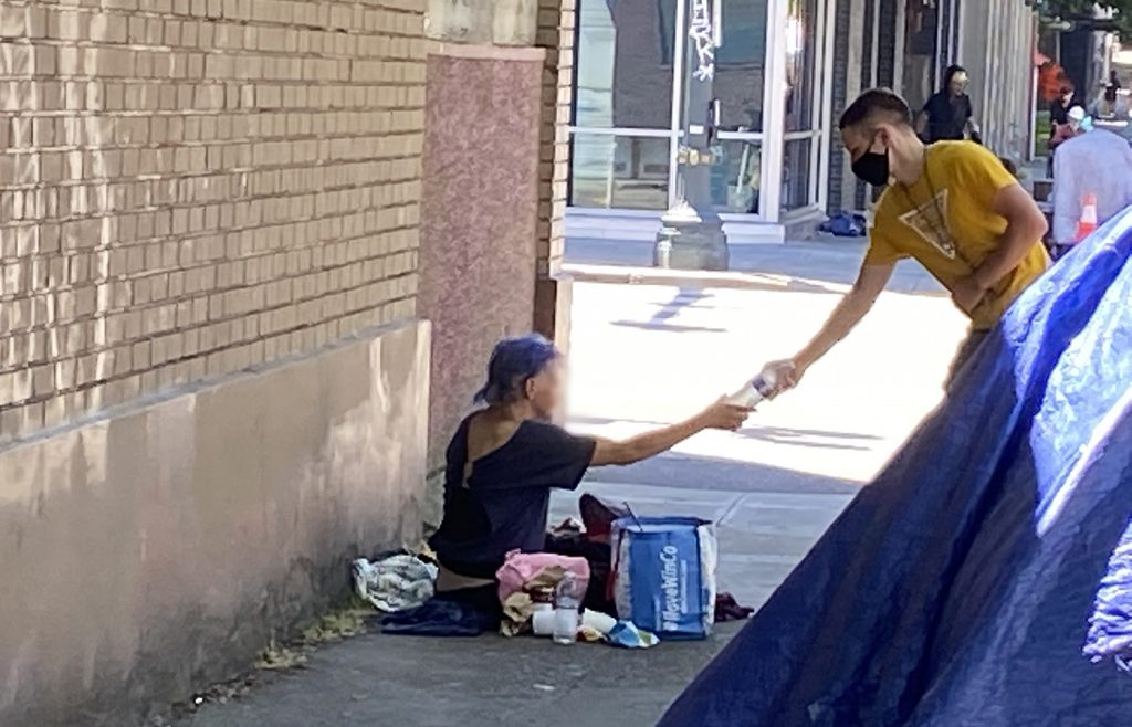 Blanchet House staff hand out water to people living homeless in Portland during the heatwave.