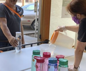 A volunteer pours water in a bowl for a homeless guest at Blanchet House in Portland.
