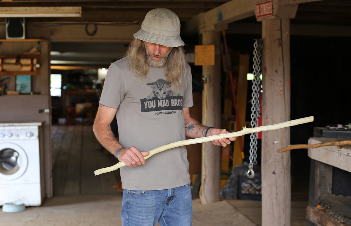 Jim holds a walking stick he's whittling at Blanchet Farm in Oregon.