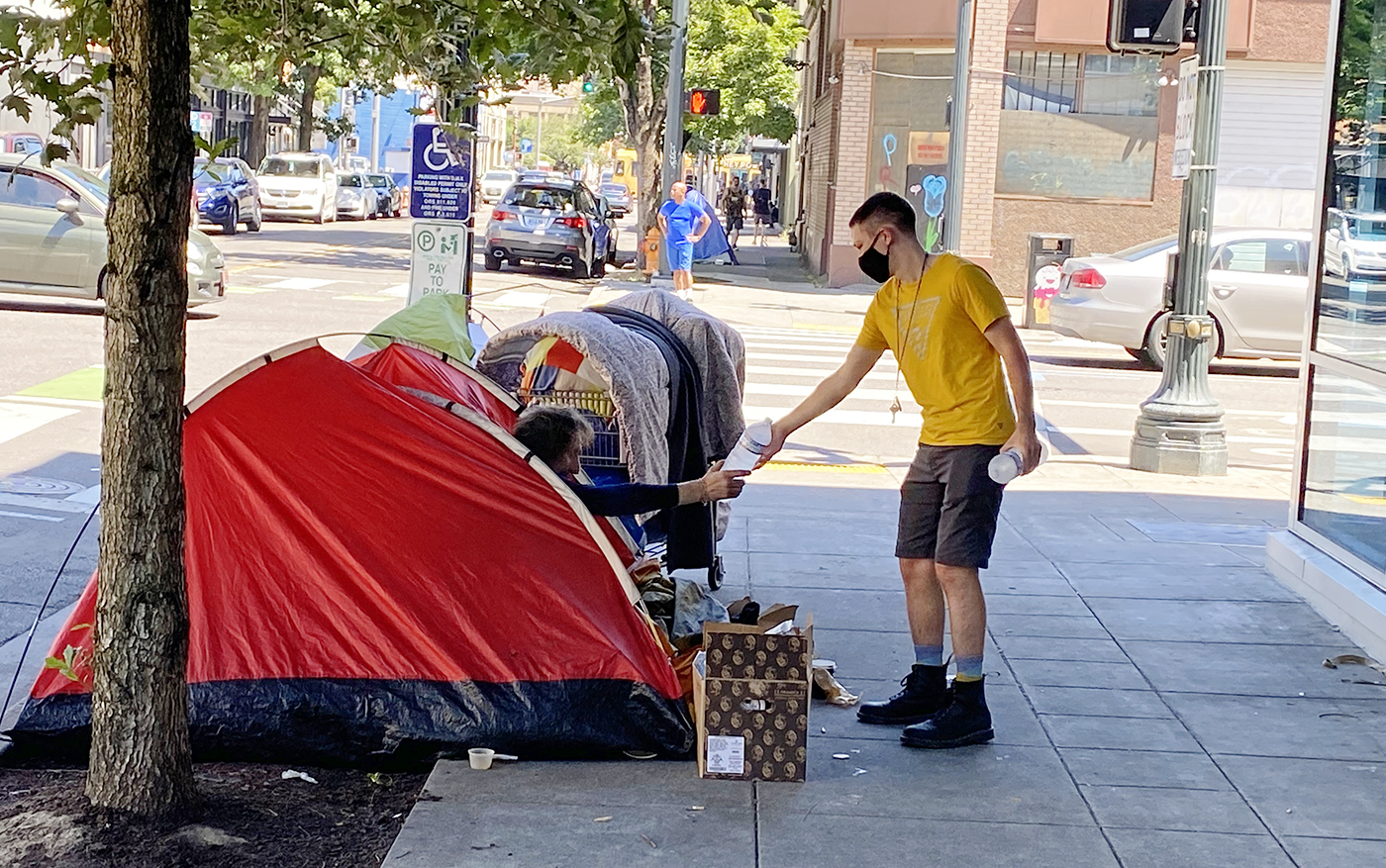 A volunteer from Blanchet House offers a bottle of water to a person sleeping in a tent during the Portland, Oregon heat wave of 2021.